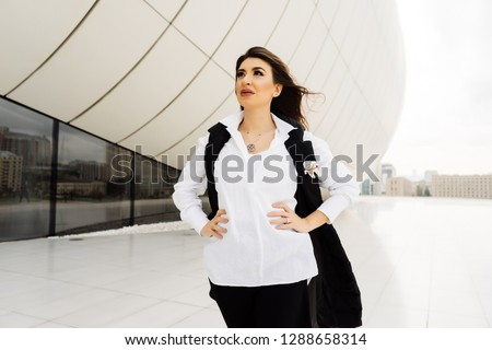 beautiful girl in a suit on a building background