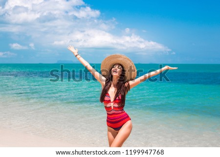 beautiful girl in a swimsuit with ethnic prints, in a straw hat against the blue sea and the beach. smiles and throws her arms out toward the sun. Summer vacation, travel, pleasure, joy