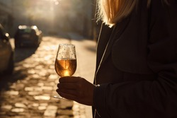 Beautiful girl in a trench coat and evening dress with a glass of wine. A girl walks in an empty morning city street at dawn after a night party. Enjoy the summer days. Celebrate the holiday alone