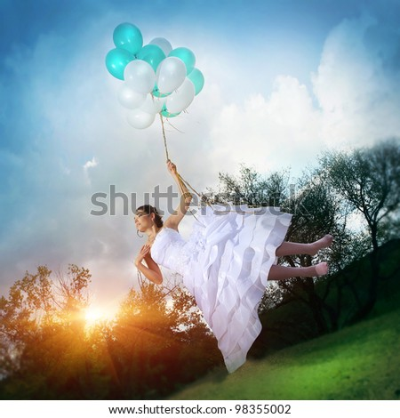 Beautiful girl in a wedding dress flying on balloons