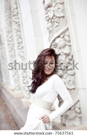 beautiful girl in a white dress near to white antique arches