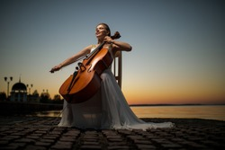 beautiful girl in a white dress playing the cello on the lake after sunset