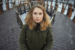 beautiful girl in a winter jacket with a hood, against the background of the park and the bridge. looking at the camera