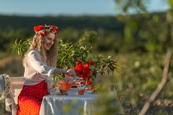 Beautiful girl in a wreath with poppies and daisies at a table in the garden and field with poppies.