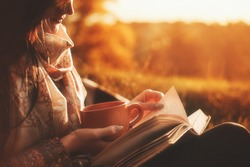 Beautiful girl in autumn forest reading a book covered with a warm blanket.a woman sits near a tree in an autumn forest and holds a book and a cup with a hot drink in her hands. Girl reading a book