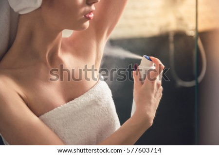 Beautiful girl in bath towel is applying deodorant while standing in bathroom after having a shower