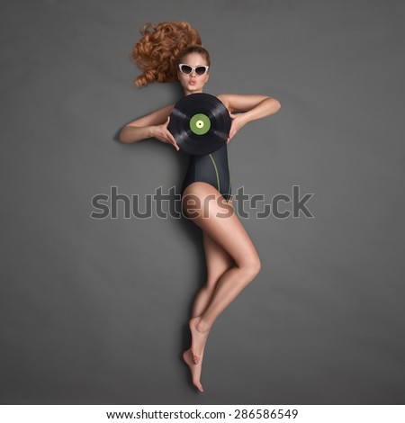 Beautiful girl in bikini and sunglasses, holding an LP microgroove vinyl record and sending a kiss on chalkboard background.