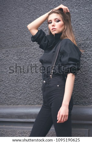 Beautiful girl in black clothes oversize with suspenders. Dark background. Toned image. #1095190625
