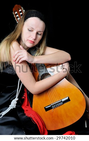 Beautiful girl in black kerchief with a guitar, on black background