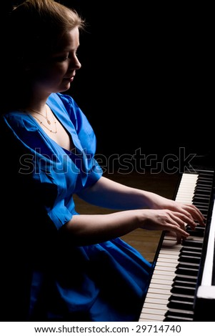 beautiful girl in blue dress playing the grand piano, isolated on black