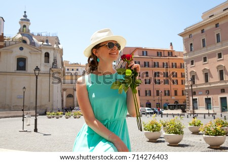 Beautiful girl in blue dress with tree roses in hand sitting on street in Rome #714276403