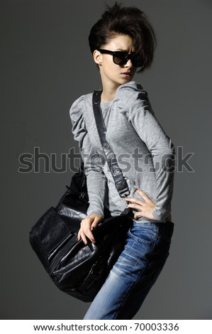 Beautiful girl in blue jeans with bag on dark background