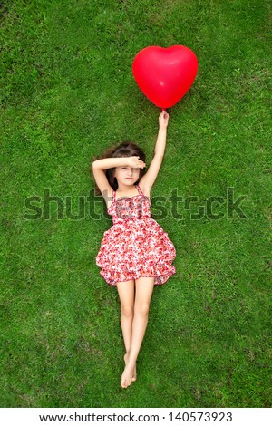 beautiful girl in color dress lying on the grass and holding a red ball in the form of heart - stock photo