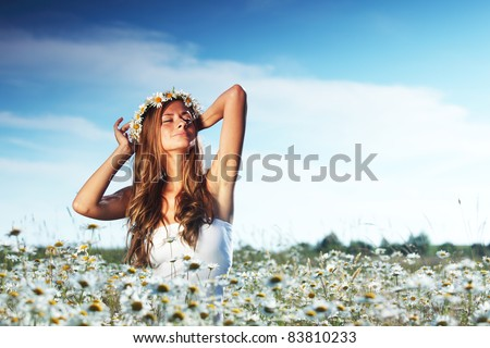 beautiful girl in dress on the daisy flowers field