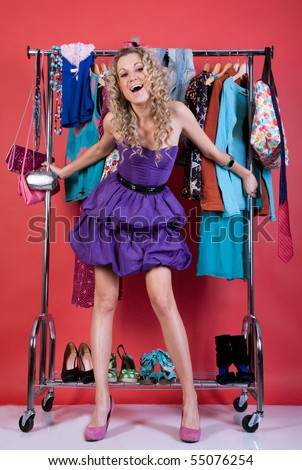 beautiful girl in fashion clothes in the dressing room on a red background