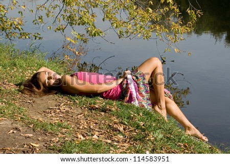 Beautiful girl in forest near pond - stock photo