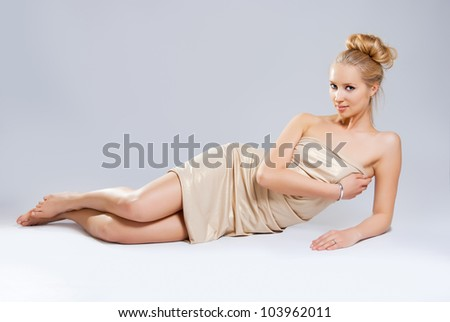 Beautiful girl in gold dress lying on a white background