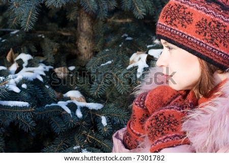 Beautiful girl in hat and mittens in snow-covered evergreens. Copy space on left. #7301782