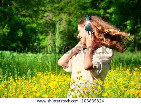 beautiful girl in headphones enjoying the music with flowing hair in a field of flowers in nature