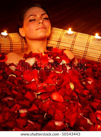 Beautiful girl in jacuzzi with rose petal and candle. Body care.