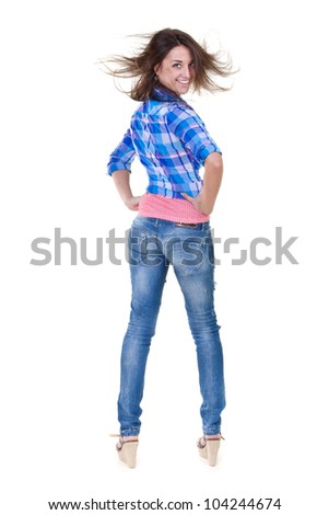 Beautiful girl in jeans turns out to back on a white background