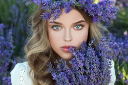 Beautiful girl in lavender wreath and retro dress on the lavender field. Beautiful woman in the lavender field on sunset in France .Girl collect lavender.Soft focus. Series.