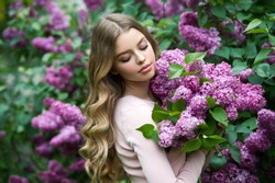 Beautiful girl in lilac Garden. Girl with lilac flowers in springtime. Gardening.