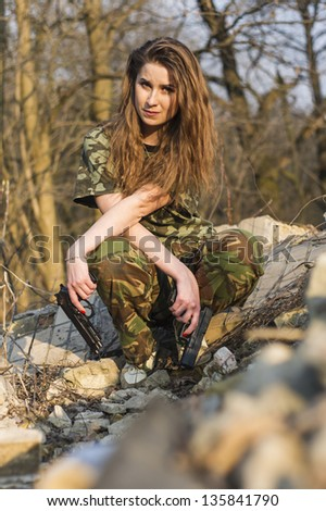 Beautiful girl in military uniform against a wall