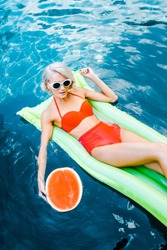 beautiful girl in pin up swimwear relaxing on green inflatable mattress in swimming pool with watermelon