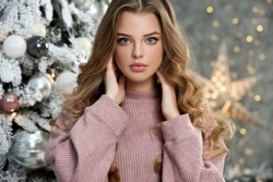 Beautiful girl in pink sweater with christmas box gift near pink and blue Christmas tree. Magical time.