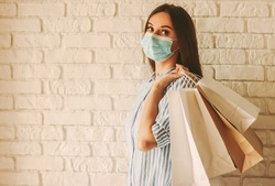 Beautiful girl in protective face mask holding shopping bags in hands. Young woman shopaholic in medical mask on face with paper bags. Female shopper. Safe shopping, coronavirus COVID-19, copy space