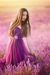 Beautiful girl in purple dress in lavender field