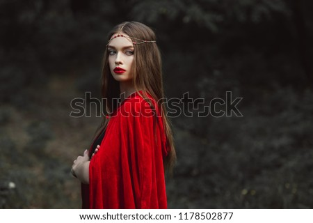 beautiful girl in red cloak and elegant wreath in woods