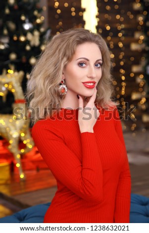 Beautiful girl in red dress on the background of bright lights. New year mood. Christmas background with a sparkly reindeer and garland #1238632021