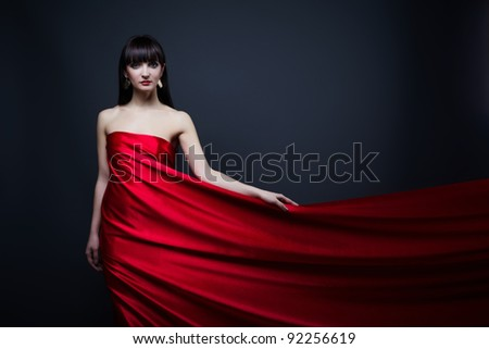 Beautiful girl in red dress over on black background