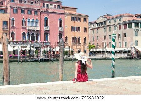 Beautiful girl in red dress standing back, in background is The Grand Canal from Venice Italy #755934022