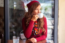 Beautiful girl in red drinking coffe in local cafe and glass of lemonade with straw on table