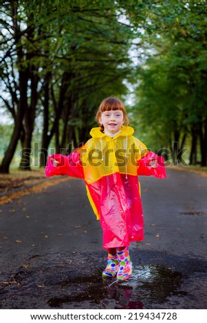 beautiful girl in rubber boots jumping in puddles