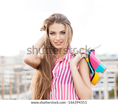 beautiful girl in sleeveless striped top messes up her long silky hair holding bright high heels