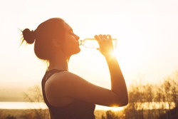 Beautiful girl in sportswear drinks water from a bottle at sunset