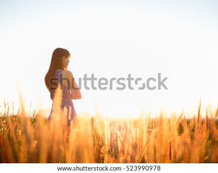 Beautiful girl in stylish summer dress walking in the field with flowers in sunlight,enjoying freedom feeling happy at sunset   #523990978