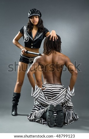 Beautiful girl in suit police and lad in suit of the prisoner - stock photo
