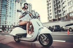 Beautiful girl in sun glasses and helmet is smiling while riding a scooter