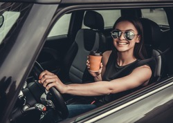 Beautiful girl in sun glasses is drinking coffee, looking at camera and smiling while sitting in her car