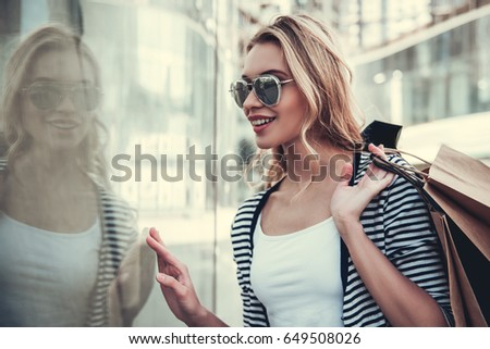 Beautiful girl in sun glasses is holding shopping bags, watching shop-windows and smiling while walking down the street #649508026