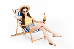 beautiful girl in sunglasses resting on beach chair with cocktail, isolated on white