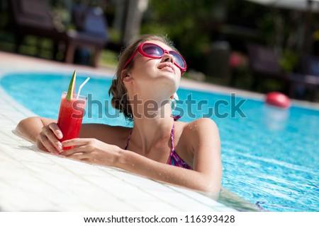 beautiful girl in sunglasses with fresh watermelon juice in luxury pool