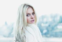 Beautiful girl in sweater freezing outdoor