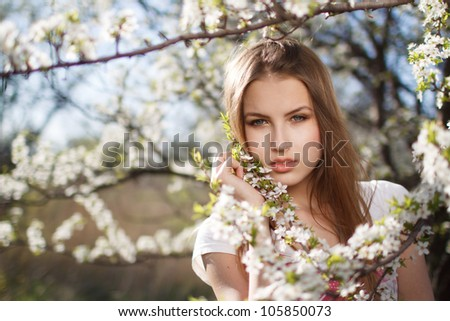 beautiful girl in the branches of apple trees