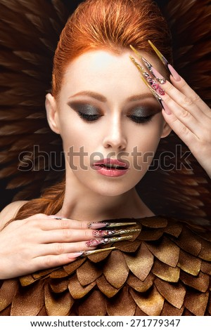 Beautiful girl in the image of the Phoenix with bright makeup, long fingernails and red hair. Beauty face. Picture taken in the studio on a black background.